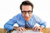 Businessman typing on his keyboard wearing glasses on white background