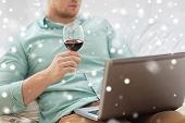 technology, drinks, leisure, home and lifestyle concept - close up of man with laptop and glass of wine at home