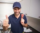Plumber smiling at the camera in the kitchen