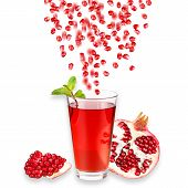 Pomegranate juice in a glass and ripe pomegranate. Isolated on white background. Close-up. Studio ph