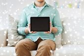 technology, leisure, people and advertisement concept - close up of man showing tablet pc computer screen sitting on sofa at home