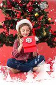 Festive little girl opening a gift against snow falling