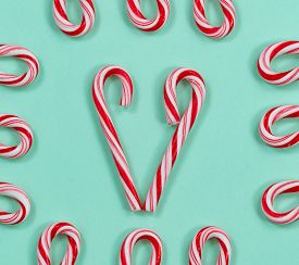 picture of candy cane border  - Image of red and white stripped candy canes on a solid light green background - JPG