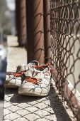 picture of chain link fence  - Pair of old worn classic sneakers hang from rusty chain link fence