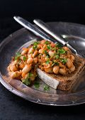 picture of stew  - Stewed white beans in tomato sauce on toasted bread selective focus closeup - JPG