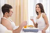 image of bed breakfast  - Smiling young couple having breakfast in bed - JPG