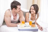 stock photo of bed breakfast  - Smiling young couple having breakfast in bed - JPG