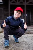 stock photo of schoolboys  - Little schoolboy thumbs up outdoor portrait in nature - JPG