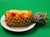 image of green papaya salad  - Thai style fruit salad inside a pineapple with a green background - JPG