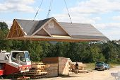 stock photo of trussle  - modular home roof being taken off foundation to put up walls and then put on top of home when done - JPG