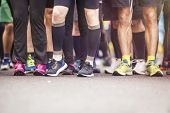 stock photo of short legs  - Detail of the legs of runners at the start of a marathon race - JPG