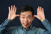 image of obscene gesture  - Funny young Asian man making face and looking at camera - JPG