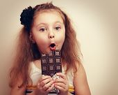 picture of unbelievable  - Surprised funny girl with open mouth and big eyes holding chocolate and looking - JPG