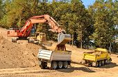 image of dump_truck  - Large track hoe excavator filling a dump truck with rock and soil for fill at a new commercial development road construction project - JPG
