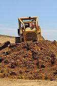 foto of bulldozer  - Large bulldozer moving rock and soil for a fill lift at a new commercial development road construction project - JPG