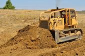 image of bulldozers  - Large bulldozer moving rock and soil for a fill lift at a new commercial development road construction project - JPG