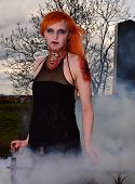 stock photo of madman  - Zombie woman with fiery hair in the old cemetery in the fog - JPG