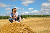 stock photo of haystack  - young boy sitting on haystack in the field and playing with his phone - JPG
