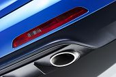 stock photo of smog  - Chrome exhaust pipe of blue powerful racing car bumper with red back lighting - JPG