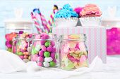 stock photo of cupcakes  - Multicolor candies in glass jars and cupcakes on color wooden background - JPG