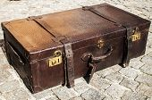 picture of paving stone  - Old closed locked retro vintage leather suitcase on stone paved surface closeup - JPG