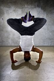 stock photo of inverted  - Inverted black breakdancer doing a headstand or handstand or urban yoga - JPG