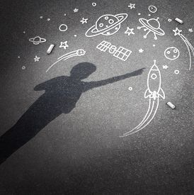 picture of child development  - Child space dream as a childhood imagination concept with a cast shadow of a kid dreaming of being an astronaut or astronomy explorer with chalk drawings of a rocket spacecraft planets stars and a flying saucer - JPG