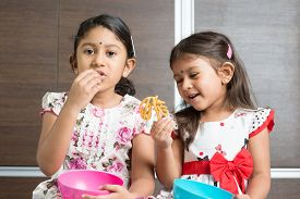 pic of malaysian food  - Two cute Indian girls eating food - JPG