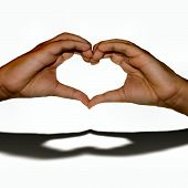 stock photo of hand heart  - Youthful hands shaped to form a heart with the shadow reflecting the heart created signaling love - JPG