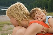 Smeary daughter hugging mother in a serene outdoors moment