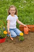 Little smiling girl gardening - planting flowers outdoors