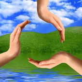 Recycling symbol made from hands on summer nature background Environment and ecology artistic concep