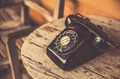 Old Telephone Black Color On Wood Table. Classic Retro Vintage Style Rotary Dial Calling Telephone T poster