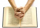 Постер, плакат: Руки молиться человека лежат на Библии