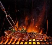 Beef raw steaks on the grill grate with fork, flames on background. Barbecue and grill, delicious fo poster