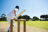 Side view of cricket player batting while playing on field against clear sky poster