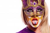 close up portrait of woman in violet mask with blue pill on tongue