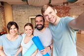 fitness, sport and healthy lifestyle concept - group of happy people with mats at yoga studio or gym poster
