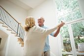 Senior couple dancing together in living room at home poster