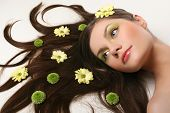 stock photo of flowing hair  - beautiful young woman lying on isolated white background with flowing hair and flowers - JPG