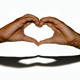 stock photo of heart shape  - Youthful hands shaped to form a heart with the shadow reflecting the heart created signaling love - JPG