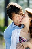 picture of young adult  - beautiful young couple kiss outdoors in the forest - JPG