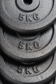 Stack Of 5kg Barbell / Dumbbell Weight Plates Inside A Weightlifting Gym poster
