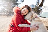 Portrait Of Tender Smiling Beautiful Asian Woman Hugging Her Pet Dog Labrador Retriever In Winter On poster