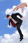 Concept photo of a businessman being dropped out of the sky by the hand of God, could be used to portray themes such as fear, fright, nightmare, refusal, dismissal, rejection, failure or disapproval.