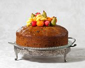 Luxury rich fruit cake on cakestand decorated with traditional marzipan fruits