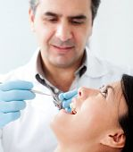 Dentist working on a female patient at his practice