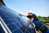 Profile Of Technician Installing Solar Panel Using Electrical Screwdriver On Blue Sky Copy Space Bac poster