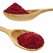 sumac powder spices on spoons isolated on a white background