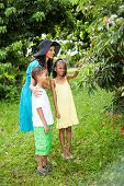 happy mother and kids in litchi orchard looking at litchis